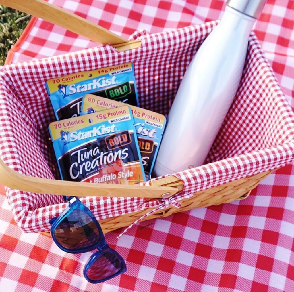Picnic basket with three pouches of Starkist tuna kits showcasing the convenience of flexible packaging.
