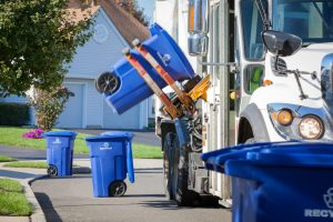 A recycling truck in a residential neighborhood is shown using it's mechanical arm to lift up a blue container containing recyclable materials. Other containers can be seen along the curbside. Canon 5D MarkII.