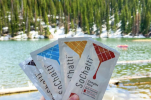SoChatti flexible packaging snack is held up in front of a lake